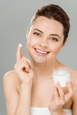 Photo for Smiling woman holding container with face cream and looking at camera isolated on grey - Royalty Free Image