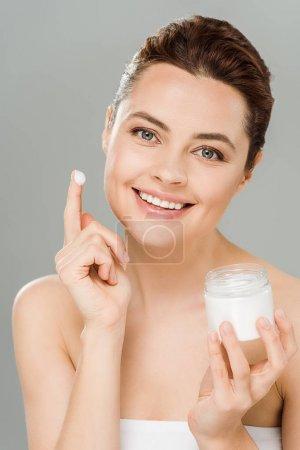 Photo pour Femme de sourire retenant le récipient avec la crème de visage et regardant l'appareil-photo d'isolement sur le gris - image libre de droit
