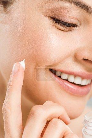 Photo pour Fermez-vous vers le haut de sourire gai de femme tout en appliquant la crème de visage - image libre de droit