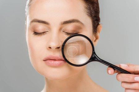 Photo pour Femme attirante avec les yeux fermés retenant la loupe près du visage d'isolement sur le gris - image libre de droit