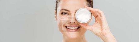 Photo pour Projectile panoramique de femme gaicouvrant l'oeil tout en retenant le récipient avec la crème de visage et souriant isolé sur le gris - image libre de droit