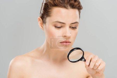 Photo pour Femme bouleversée et nue retenant la loupe d'isolement sur le gris - image libre de droit