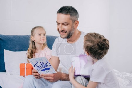 Photo for Cute daughter and son sitting with gift boxes near smiling dad holding fathers day greeting card - Royalty Free Image