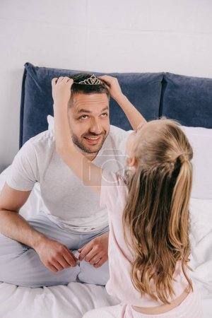Photo for Cute daughter putting diadem on smiling daddy on fathers day - Royalty Free Image