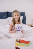 "Постер, картина, фотообои ""cute kid drawing fathers day greeting card while sitting on bedding and looking at camera"""