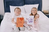 "Постер, картина, фотообои ""adorable children holding fathers day greeting cards while sitting on bedding and smiling at camera"""