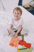 "Постер, картина, фотообои ""adorable child making fathers day greeting card with i love you dad inscription and heart symbol while smiling at camera"""