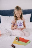 "Постер, картина, фотообои ""adorable child drawing fathers day greeting card while sitting on bedding near multicolored paper"""