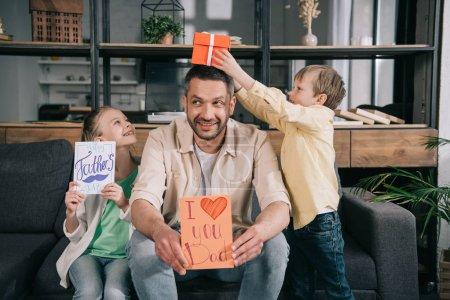 Photo pour Enfants heureux avec des cadeaux de jour de père s'amusant avec la carte de voeux de fixation de père avec je t'aime l'inscription de papa et le symbole de coeur - image libre de droit