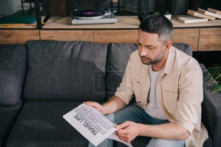 Photo pour L'homme attentif lisant le journal de vie de voyage tout en s'asseyant sur le sofa à la maison - image libre de droit