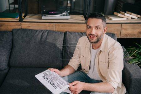 Foto de Guapo hombre barbudo sonriendo a la cámara mientras se sienta en el sofá y la celebración de la vida de viaje periódico - Imagen libre de derechos