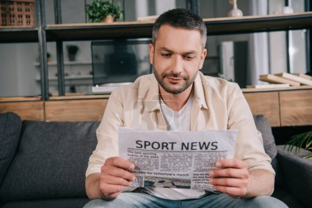 Photo for Handsome man reading sport news newspaper while sitting on sofa at home - Royalty Free Image