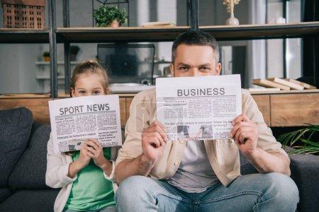 Foto de Hija alegre y padre cubriendo caras con periódicos de noticias de negocios y deportes - Imagen libre de derechos