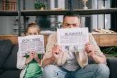 cheerful daughter and father covering faces with business and sport news newspapers