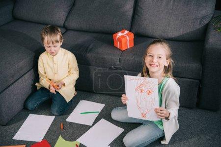 Foto de Chica alegre mostrando dibujo y sonriendo a la cámara mientras está sentado en el suelo cerca de hermano - Imagen libre de derechos