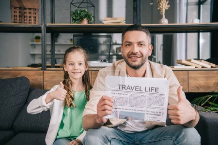 Foto de Smiling father and daughter showing thumbs up while sitting on sofa with travel life newspaper - Imagen libre de derechos
