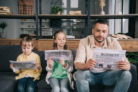 Foto de Padre con niños adorables leyendo periódicos mientras se sienta en el sofá en casa - Imagen libre de derechos