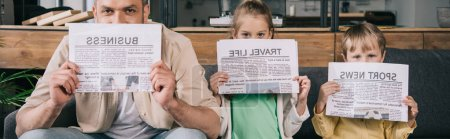 Photo for Panoramic shot of cheerful father and kids covering faces with newspapers - Royalty Free Image