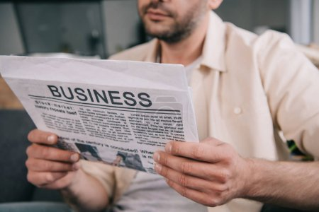 Photo pour Cropped shot of bearded man reading business newspaper at home - image libre de droit