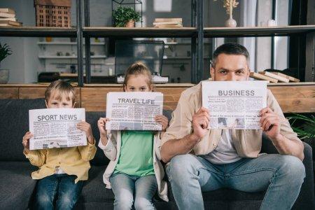 Foto de Padre alegre y los niños sosteniendo periódicos mientras se sienta en el sofá en casa - Imagen libre de derechos