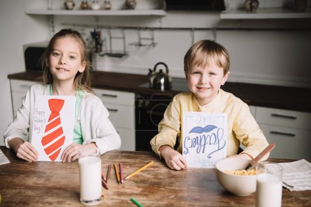 Photo for Smiling brother and sister showing fathers day greeting cards while sitting at kitchen table with served breakfast - Royalty Free Image