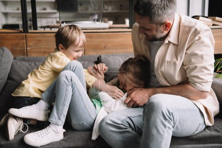 Photo for Happy father with cheerful children having fun on fathers day on sofa at home - Royalty Free Image