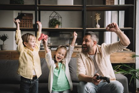 Photo for KYIV, UKRAINE - MAY 10, 2019: Happy family celebrating triumph while playing video game with joysticks at home. - Royalty Free Image