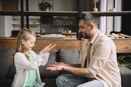 Photo for Cheerful dad with adorable daughter having fun while sitting on sofa at home - Royalty Free Image