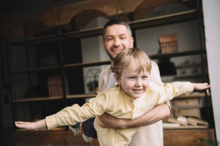 Photo for Happy daddy having fun with adorable smiling son at home - Royalty Free Image