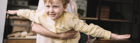 Photo for Panoramic shot of man having fun with adorable smiling son at home - Royalty Free Image