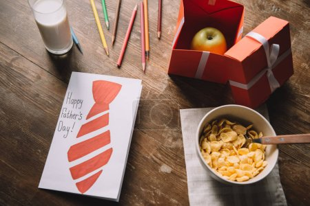 Photo for Fathers day greeting card, apple in gift box, pencils, bowl with flakes and glass of milk on wooden tabletop - Royalty Free Image