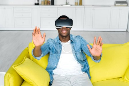 Photo for High angle view of happy african american man in vr headset sitting on couch - Royalty Free Image