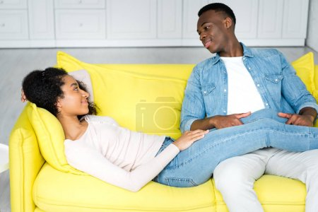 Photo for African american woman lying on couch and looking at boyfriend - Royalty Free Image