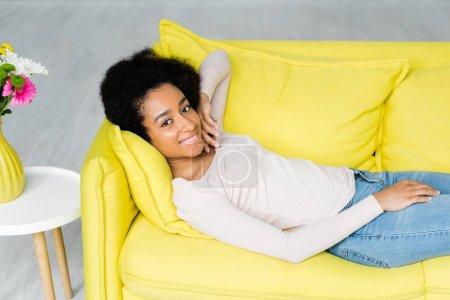 Photo pour Vue d'angle élevé de la femme américaine africaine se trouvant sur le divan et regardant l'appareil-photo - image libre de droit
