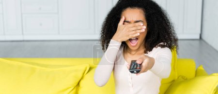 african american woman with remote controller in hand covering face