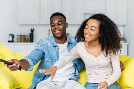 Photo pour Homme américain africain retenant le contrôleur à distance dans la main et passant le week-end avec la petite amie - image libre de droit