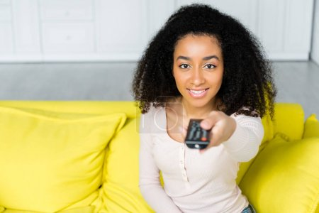 high angle view of happy african american woman holding remote controller in hand