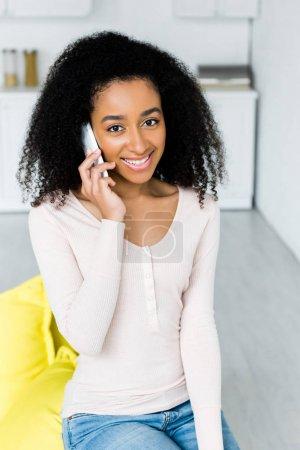 Photo pour Femme américaine africaine heureuse parlant sur le smartphone, et regardant l'appareil-photo - image libre de droit