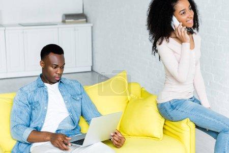 Photo pour Homme afro-américain en utilisant un ordinateur portable, tandis que la femme parle sur smartphone - image libre de droit