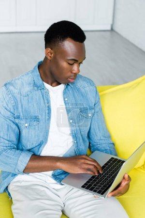 Photo pour Vue d'angle élevé de l'homme américain africain utilisant l'ordinateur portatif à la maison - image libre de droit