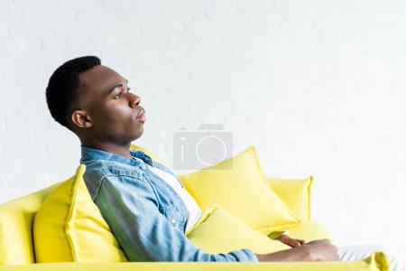 Photo pour Vue de côté de l'homme américain africain calme s'asseyant sur le divan à la maison - image libre de droit
