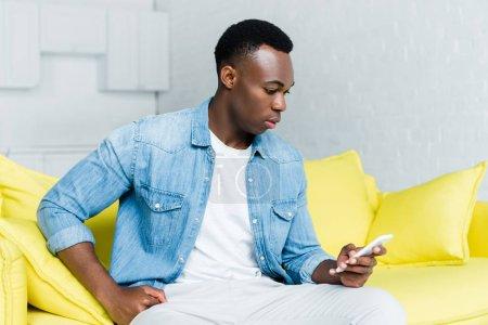Photo pour Vue latérale de l'homme afro-américain en utilisant un smartphone - image libre de droit