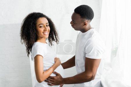 Photo pour Vue latérale de l'homme américain africain touchant le ventre enceinte amie - image libre de droit