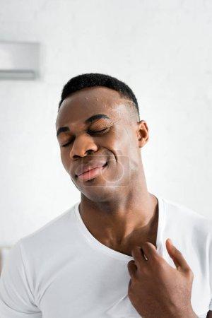 Photo pour Homme américain africain épuisé fermant les yeux et restant dans la pièce avec la température de chaleur - image libre de droit