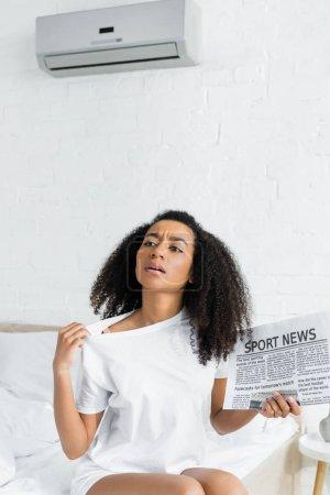 Photo pour Femme américaine africaine moite s'asseyant sur le lit dans la pièce avec la température de chaleur et la condition d'air - image libre de droit