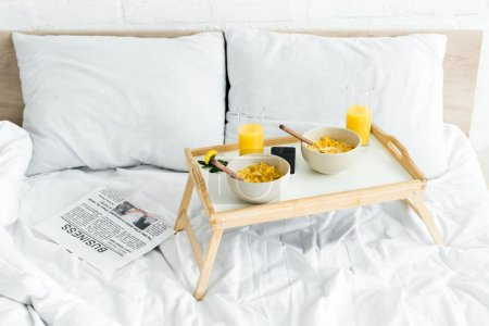 Photo for High angle view of tray table with breakfast on white bed in bright room - Royalty Free Image