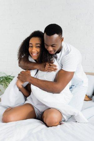 Photo pour Homme afro-américain étreignant sa charmante petite amie, assis sur un lit blanc - image libre de droit