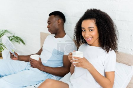 Photo for Selective focus of african american couple spending time in bed, reading newspaper, holding cup with beverage - Royalty Free Image