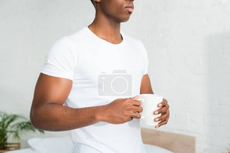 Photo for Cropped view of african american man holding cup in hands, standing in white room - Royalty Free Image