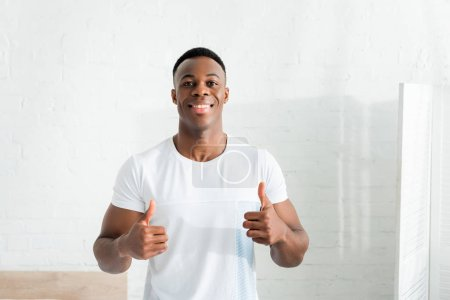 front view of happy african american man showing thumbs up, looking at camera
